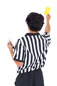 Stern referee showing yellow card on white background