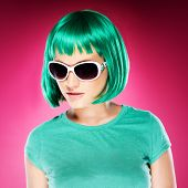 Trendy beautiful young woman in sunglasses with an iridescent green hairstyle and matching t-shirt,