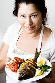 Female chef shows sea bream fish