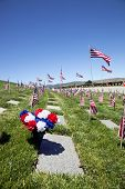 picture of headstones  - American flags headstones flowers and flying Coffin Flags each one once presented at military funeral service.