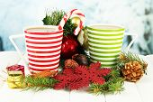Cups of hot cacao with chocolates and Christmas decorations on table on bright background