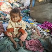 KATHMANDU, NEPAL - DEC 22, 2013: Unidentified child is sitting while her parents are working on dump