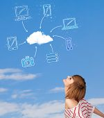 Casual young girl looking at cloud computing concept on blue sky