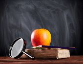 Still life of school tools and books with blackboard on background
