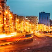 Colorful sunset in Old Havana with  the street lights of El Malecon and light trails from the passin