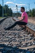 Single man in pink t-shirt sitting on train tracks