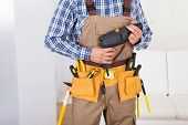 Man Wearing Tool Belt At Home