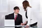 Businessman Looking At Female Colleague While Smiling At Desk