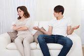 Portrait Of Couple Sitting On Sofa Having Quarrel