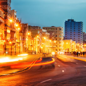 stock photo of malecon  - Colorful sunset in Old Havana with  the street lights of El Malecon and light trails from the passing cars - JPG