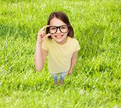 education, school, people, childhood and vision concept - smiling little girl in black eyeglasses over grass background