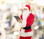 christmas, holidays, technology and people concept - man in costume of santa claus with tablet pc computer over lights background