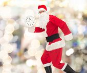 christmas, holidays and people concept - man in costume of santa claus running with clock showing twelve over lights background