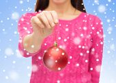 christmas, decoration, holidays and people concept - close up of woman in pink sweater holding red christmas ball over blue background with snow
