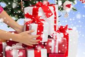 winter holidays, celebration and people concept - close up of woman putting present under christmas tree over blue background with snow