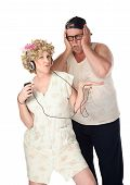 image of wife-beater  - Wife listening to music while husband covers his ears - JPG