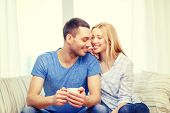love, family, healthy food and happiness concept - smiling man with cup of tea or coffee with wife or girlfriend at home