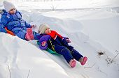 pic of snow-slide  - Two little girls on a sled sliding down a hill on snow in winter - JPG