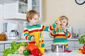 Two Funny Children Cooking Italian Meal With Spahetti