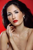 image of red-necked  - Attractive brunette woman with magnificent hair on red background touches her neck - JPG