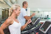 Side view of a fit young couple running on treadmills at the gym