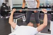 Personal female trainer helping young man with lifting barbell in the gym