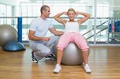 Full length of a male trainer assisting woman with abdominal crunches at the gym