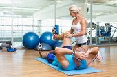 Female trainer assisting young man with exercises at fitness studio