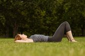 Pretty redhead lying on grass in park