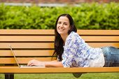 Casual brunette lying on bench typing on laptop in the park