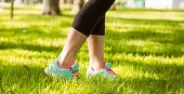 Woman in running shoes stepping on grass in the park