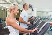 Side view mid section of a fit young couple running on treadmills at the gym