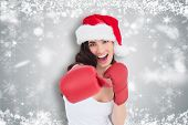 Festive brunette in boxing gloves punching against white snowflake design on grey