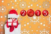 Brunette in red gloves and santa hat showing gift against snowflake wallpaper pattern