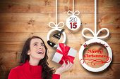 Happy brunette in red jumper hat showing a gift against christmas decorations over wood