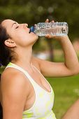 Fit brunette in sportswear drinking water in the park