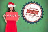Brunette in red dress holding sale sign against green christmas tree pattern