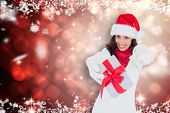 Excited brunette in santa hat giving gift against light design shimmering on red