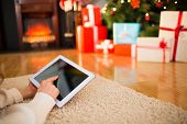 Redhead woman lying on floor using tablet at christmas at home in the living room