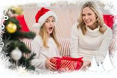 Festive mother and daughter on the couch with gift against frost frame