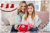 Daughter opening christmas gift with mother against christmas themed frame