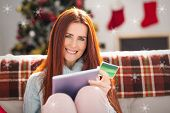 Festive redhead shopping online with tablet against snowflakes