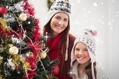 Mother and daughter decorating christmas tree against snow falling
