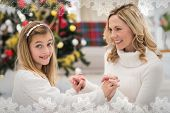 Festive mother and daughter beside christmas tree against snowflake frame