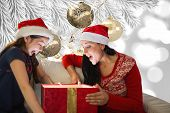 Mother and daughter opening gift against christmas decorations hanging from branch