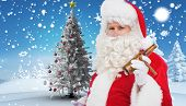 Santa claus holding beer and cigar against christmas tree in snowy landscape
