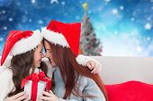 Mother and daughter with gift against blurry christmas scene