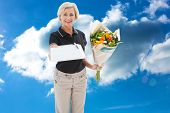 Happy flower delivery woman looking for signature against cloudy sky