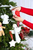 Woman decorating Christmas tree, close-up, on light background