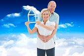 Happy older couple holding house shape against bright blue sky with clouds